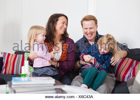 Smiling parents and daughters (2-4) in playful mood - Stock Photo