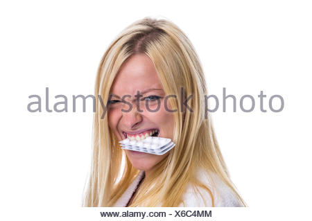 Woman with pills in her mouth - Stock Photo