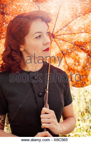 Sweden, Redheaded woman holding umbrella - Stock Photo