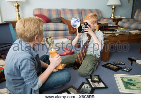 Brothers playing with old camera and trophy memorabilia - Stock Photo