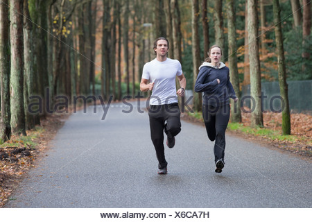 Couple running through forest - Stock Photo