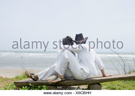 Young couple sitting on a wooden plank on the beach - Stock Photo