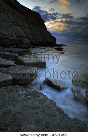 View of rock formations and cliffs in rugged bay at sunset, Dunraven Bay, Southerndown, Glamorgan Heritage Coast, South Wales, - Stock Photo