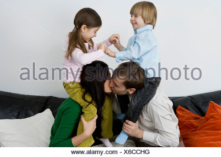 Two parents carrying children on their shoulders and kissing - Stock Photo