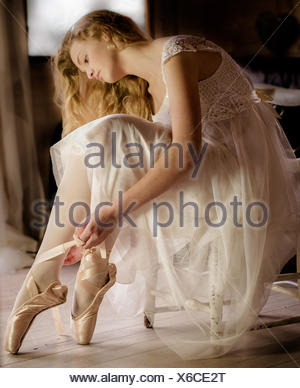 Young ballet dancer in white dress preparing ribbons on ballet shoes - Stock Photo
