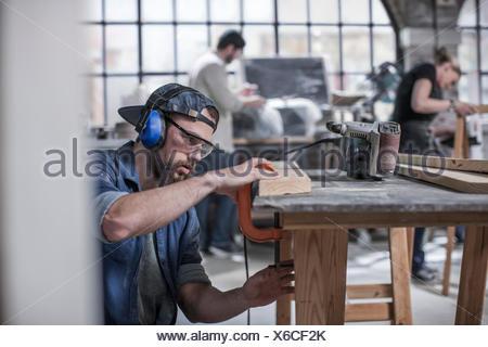 Carpenter sanding at workbench in antique restoration workshop - Stock Photo