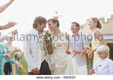 Guests throwing rose petals on bride and groom - Stock Photo