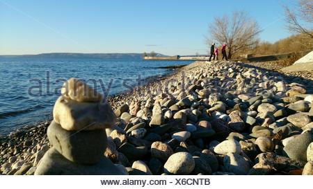 People Walking On Pebble Beach Against Clear Blue Sky - Stock Photo