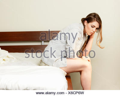 Sullen young woman sitting on hotel bed - Stock Photo