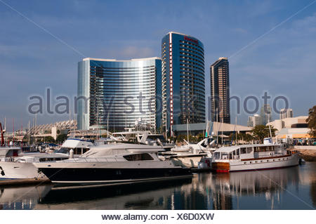 Boats anchored in a harbor marina within walking distance of modern hotels. - Stock Photo