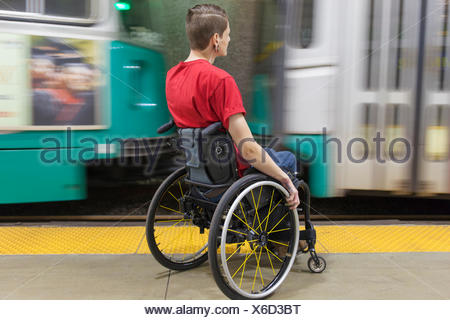 Trendy man with a spinal cord injury in wheelchair waiting for a subway train - Stock Photo