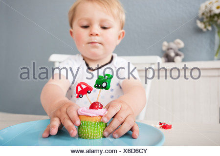 Baby boy playing with cupcake - Stock Photo