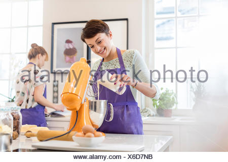 Female caterer baking, using stand mixer in kitchen - Stock Photo