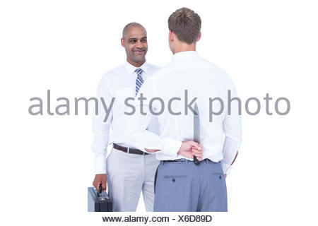 Businessman holding knife behind his back - Stock Photo