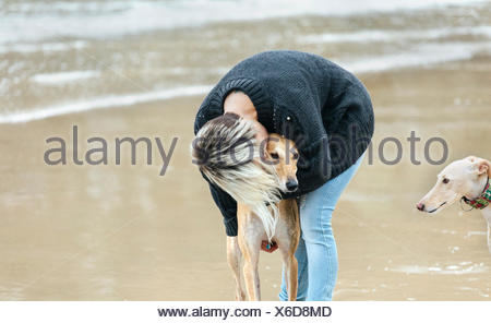 Spain, Llanes, young woman kissing her greyhound on the beach - Stock Photo