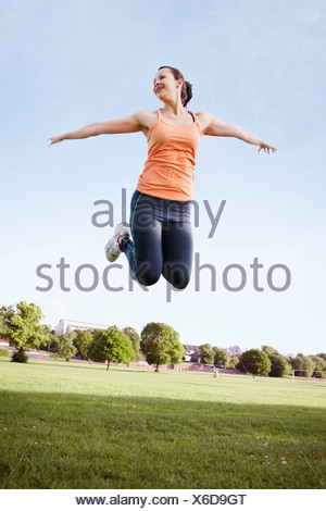 Woman jumping in park - Stock Photo
