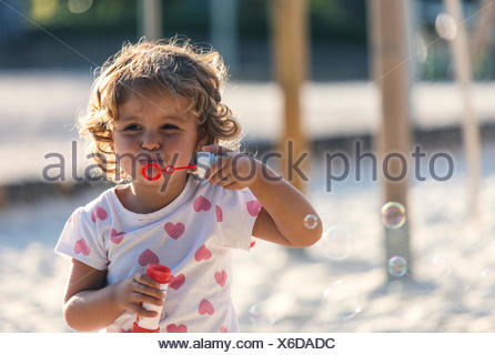 Little girl making soap bubbles at playground - Stock Photo