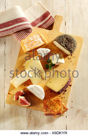 Assortment of soft and semi-hard cheeses on a cheeseboard with sliced fresh figs and toast for a gourmet appetizer to a meal, view from above - Stock Photo