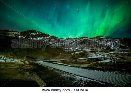 Aurora Borealis or Northern lights over geothermal area Krysuvik-Seltun, located on the Reykjanes Peninsula, Iceland - Stock Photo