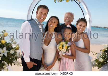 Bride and Groom with family on beach, (portrait) - Stock Photo