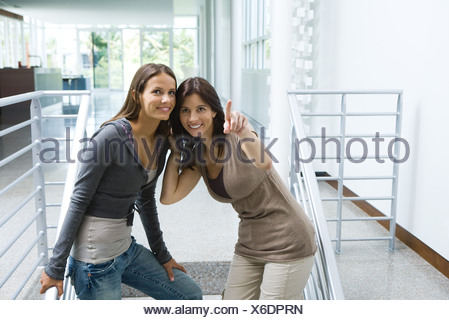 Woman standing on stairs with daughter, pointing, both looking up and smiling - Stock Photo
