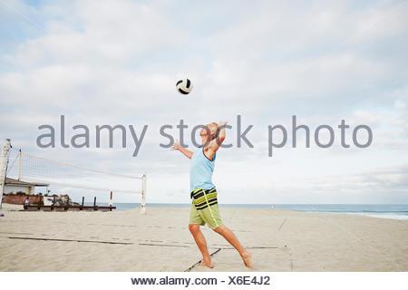 Mature man standing on a beach, playing beach volleyball. - Stock Photo