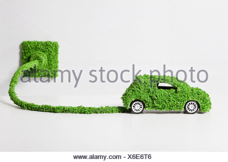 Electric car covered with grass connected to socket, close up - Stock Photo