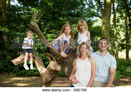 Family with three children by a tree in a forest, posing for a picture. - Stock Photo