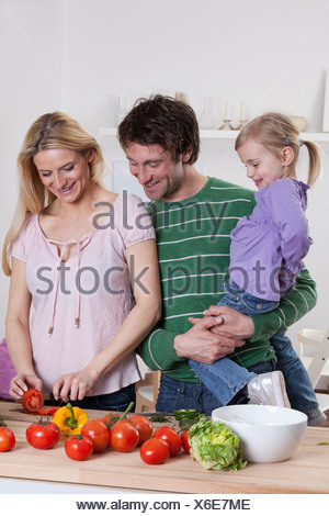 Germany, Bavaria, Munich, Mother preparing salad with father and daughter standing beside her - Stock Photo