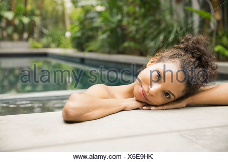 Woman resting at the edge of swimming pool - Stock Photo