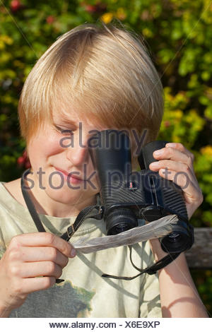 boy using a reversed binocular as a magnifier and looks at a feather, Germany - Stock Photo