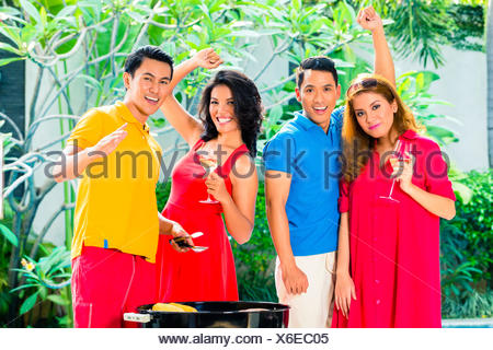 Asian friends celebrating pool party with music, wine and barbecue or BBQ - Stock Photo