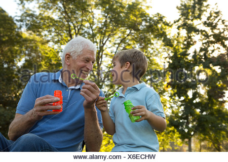 Grandfather and grandson blowing bubbles - Stock Photo
