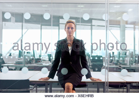 Portrait of serious blonde businesswoman sitting at edge of table in conference room - Stock Photo