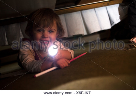 Young girl playing with torch underneath bed - Stock Photo