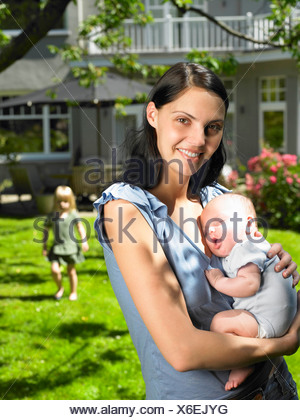 Mother and kids in the garden - Stock Photo