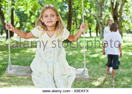 Girl playing on swing in park - Stock Photo