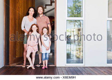 Family smiling at front door - Stock Photo