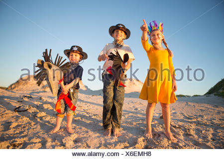 Sister and brothers dressed as native american and cowboys pointing from sand dunes - Stock Photo