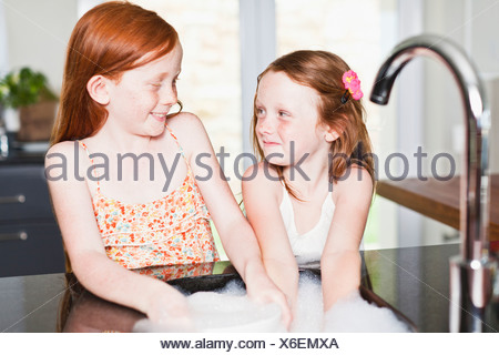 Smiling girls washing dishes in sink - Stock Photo