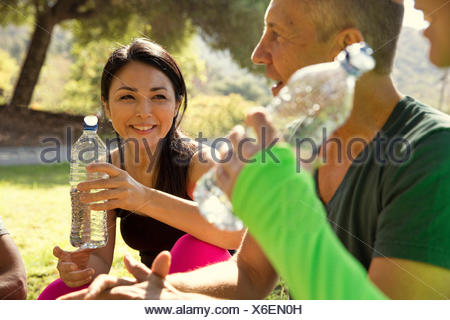 Mature male and female runners taking a water break in park - Stock Photo