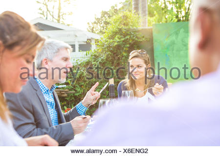 Mature adults eating and talking together at garden party table - Stock Photo