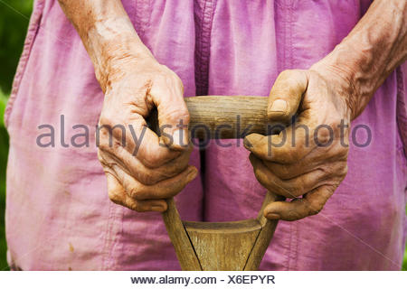 A woman holding a shovel on a farm. - Stock Photo