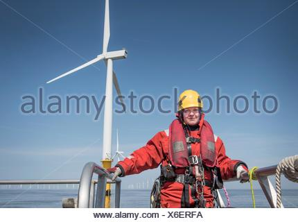 Portrait of female engineer on boat at offshore windfarm - Stock Photo