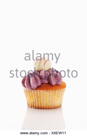 Close up of buttercream black currant cupcake with chocolate truffle against white background - Stock Photo
