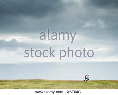 Two women jogging along the coast runners - Stock Photo