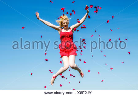Portrait of woman jumping in the air with rose petals - Stock Photo
