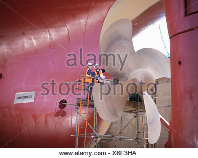 Workers examining ship turbines on site - Stock Photo