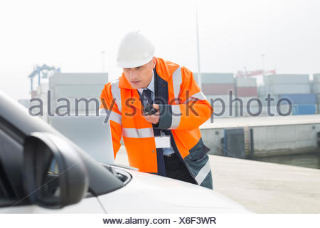 Middle-aged man talking on walkie-talkie while using laptop in shipping yard - Stock Photo