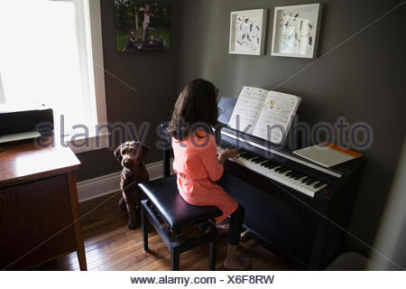 Dog waiting for girl playing piano - Stock Photo